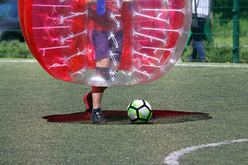 man on a sports field playing in the bumper ball