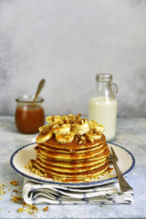 Homemade hot banana pancakes with caramel sauce and nuts.