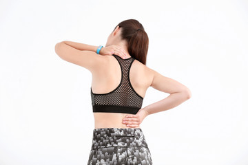 Woman in sportswear suffering from back pain on white background