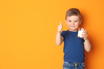 Cute little boy with glass of milk on color background