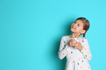 Cute little girl with glass of milk on color background