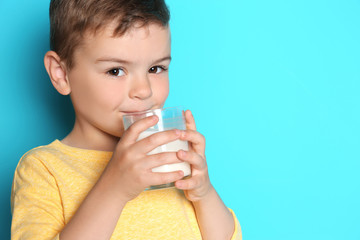 Cute little boy drinking milk on color background