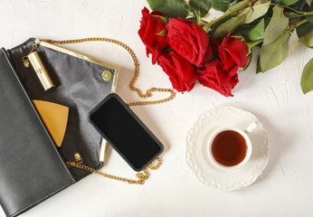 Cup of tea, woman's bag and red roses on white background. Flat lay, top view.