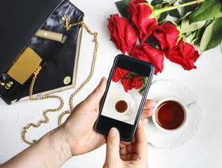 Woman using smartphone to take photos of roses and cup of tea