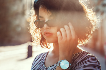 Outdoor close up portrait of young beautiful stylish curly girl wearing black narrow sunglasses, silver wrist watch, striped dress. Model walking in street. Sunny day light. Summer fashion concept