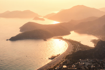 Wall Mural - Beautiful seascape at sunset. Landscape with sea, mountains, islands, city, gold sunlight and orange sky in summer. Amazing view from the mountain peak on Oludeniz, Turkey. Travel and resort. Nature