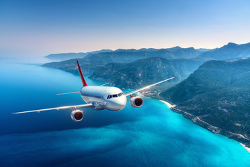 Poster Avion à Moteur Airplane is flying over islands and sea at sunrise in summer. Landscape with white passenger airplane, seashore, mountains, sky, and blue water. White passenger aircraft. Travel and resort. Tourism