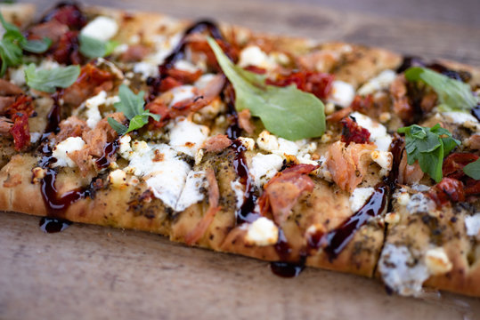 Detailed photo of Pasture Pesto Flatbread with Smoked Chicken, Sun-dried Tomatoes, Fresh Mozzarella and  Arugula Balsamic Glaze on rustic wooden board. Top View (Above). Close up.