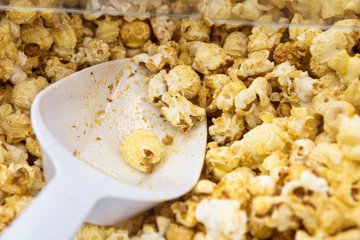 fresh sweet popcorn and shovel in a popcorn machine, close up