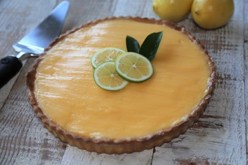 French style Lemon tart  placed next to fresh lemons on white wooden background
