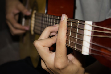 Close up of young man playing guitar.
