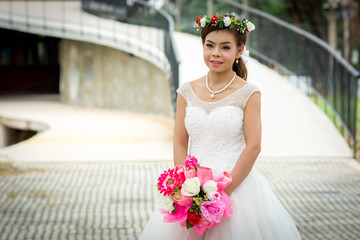 9619ce26478 Woman wearing a wedding dress and with holding a bouquet of flowers  standing on cement floor