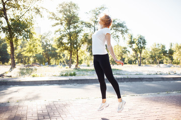 young athletic girl doing exercise, posing in a jump, can be used for advertising, text insertion