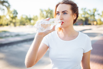 Young sports girl, drinking water from the bottle, after a hard workout, can be used for advertising, text insertion