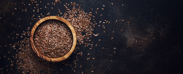 Raw flax seeds in bowl, stone background, top view