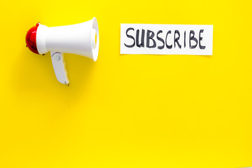 Subscribe template or mockup. Hand lettering subcribe near megaphone on yellow background top view space for text