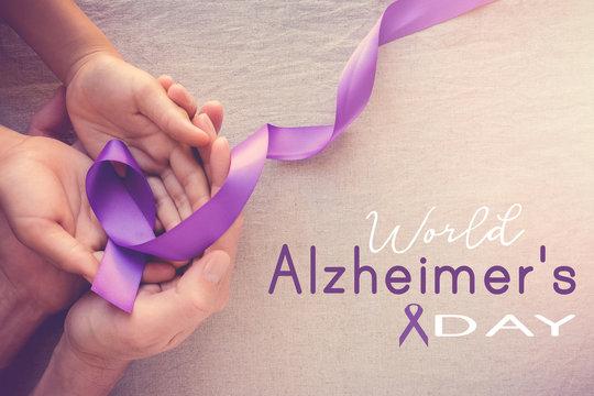 Hands holding Purple ribbons, world Alzheimer's day