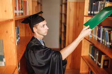 Successful graduate guy, in academic dresses, posing in the library, holding a green folder, can be used for advertising, text insertion
