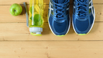 A freshly prepared drink made of lemon and mint on the background of sneakers wooden floor. The view from the top. Flat lay.