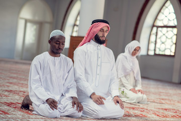 Two religious young people praying inside the mosque. islamic