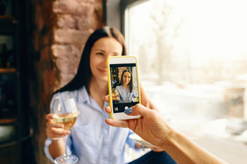 Woman taking photo her beautiful young girl friend glass wine on smartphone