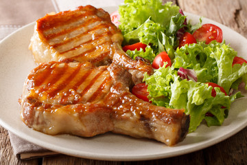 grilled chop pork honey glaze, served with a salad of fresh vegetables close-up on a plate. horizontal