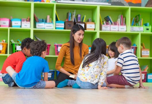 Asian female teacher teaching mixed race diversity group of kids reading book sitting on library floor in classroom,Kindergarten pre school concept.