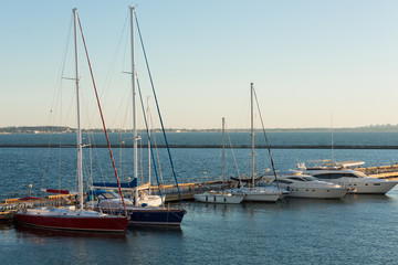 pleasure yachts moored in the harbor at the pier, six pleasure boats, early morning, concept summer and travel