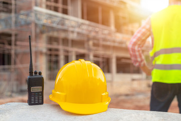 Radio and helmet in construction site and construction site worker background safety first concept