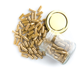 Herbal medicine capsule from glass bottle on white background