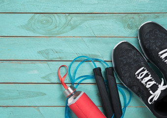 Skipping rope,Running shoes and drink bottle on wood background,top view
