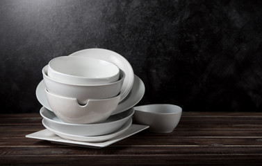 Stack of white ceramic dishware on wood against black cement wall