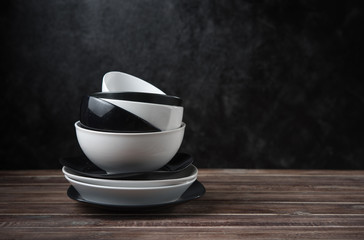 Stack of white and black ceramic dishware on wood against black cement wall