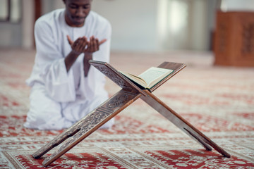 Black African Muslim Man Is Praying In The Mosque with open holy book of Koran