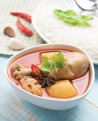 Spicy Muslim chicken curry,Thai massaman curry in a bowl and rice on wood background