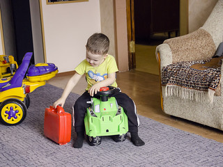 a little boy with a red suitcase is sitting on a toy car
