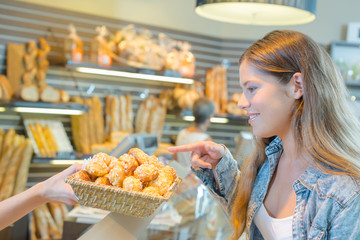 Lady pointing to cakes in bakery