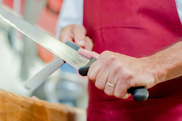 man sharpening knife with a steel