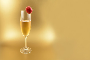Glass of champagne with strawberry stock images. Champagne on a golden background with copy space for text. Festive golden background
