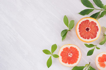Summer fresh background - round slices pink grapefruits and green leaves on white wood board, top view, copy space.