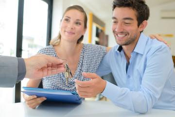 Estate agent handing keys to happy couple