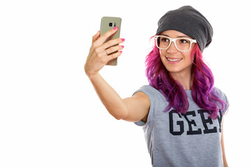 Studio shot of happy geek girl smiling while taking selfie pictu