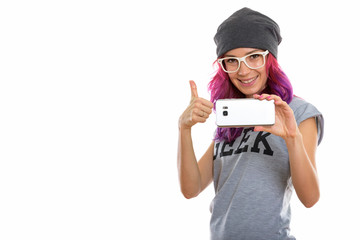 Studio shot of happy geek girl smiling while taking picture with