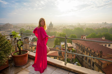 Woman standing on terrace and overlooking city in early morning