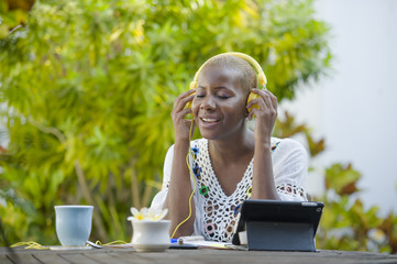young beautiful and happy black African American woman enjoying outdoors at cafe working with digital tablet listening to music with headphones
