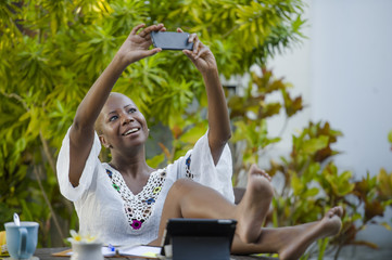 young happy and attractive black afro American woman working with digital tablet outdoors at cafe taking selfie picture with mobile phone relaxed