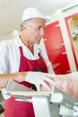 butcher slicing a block of meat using a machine
