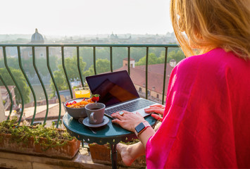 Woman using laptop during breakfast on balcony
