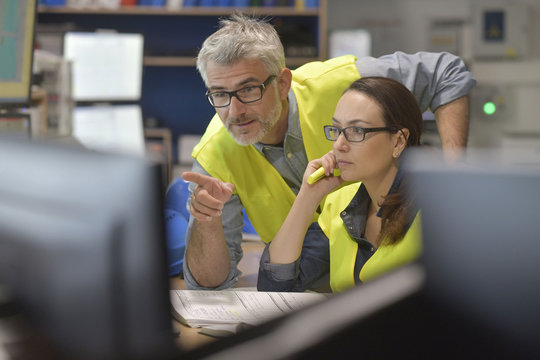 Technicians working in industrial plant control room