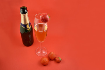 Champagne with strawberries stock images. Strawberries with champagne. Champagne on a red background with copy space for text. Festive red background. Valentines Day concept